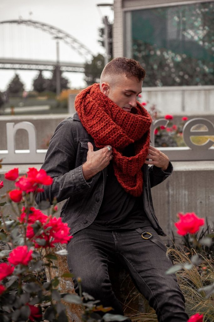 A man wearing a super bulky, rust colored crocheted infinity scarf. His hands are on the lapel of his black denim jacket and looking down. He is surrounded by bright red flowers.
