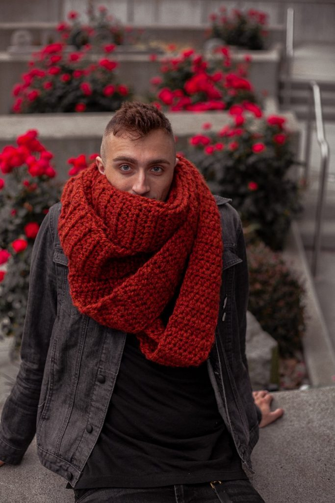 A blue eyed guy with a black jacket and rust colored super bulky infinity scarf looking directly at the camera.