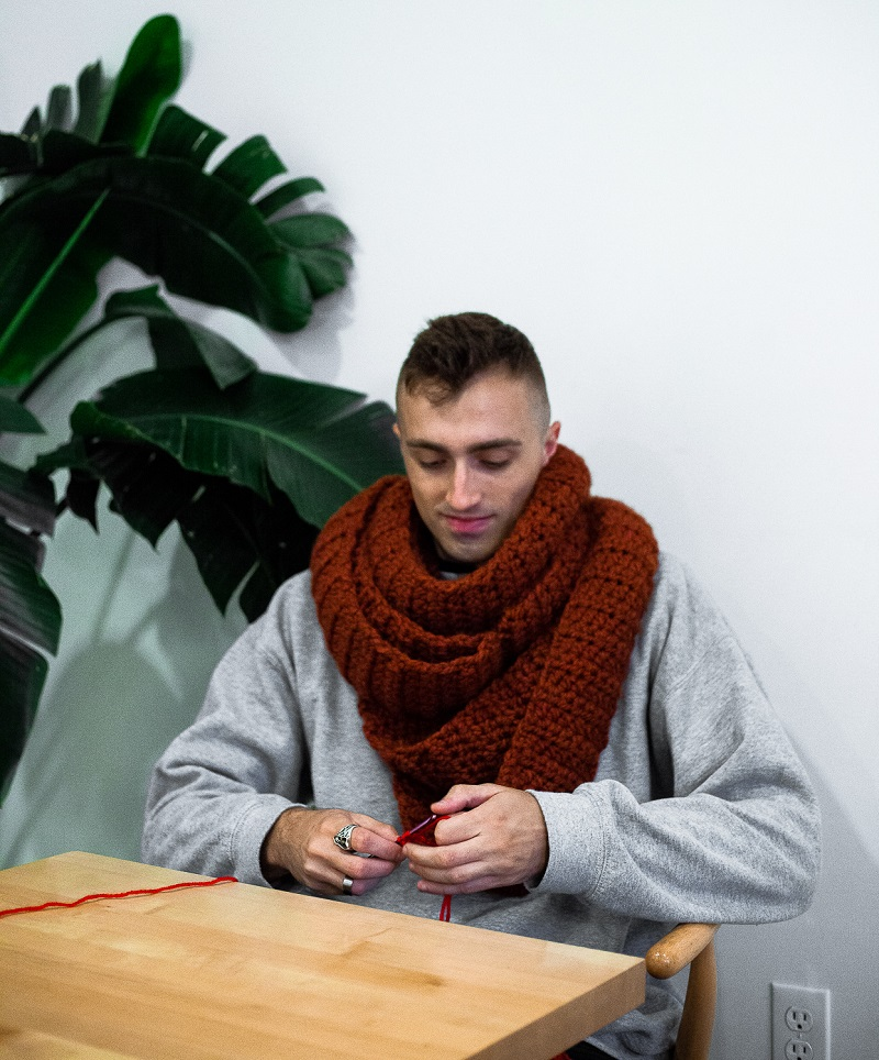 Photo of guest designer Vincent Green-Hite who is behind Knot Bad Ami and yarn Punk sitting on a wooden chair crocheting