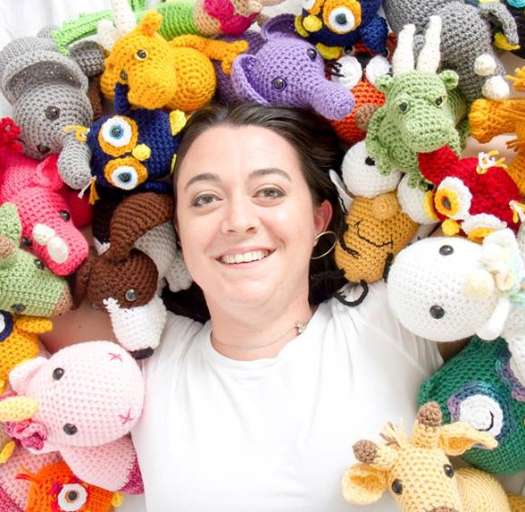 Photo of guest designer Kati Brown surrounded with a lot of crochet amigurumi stuffed toys