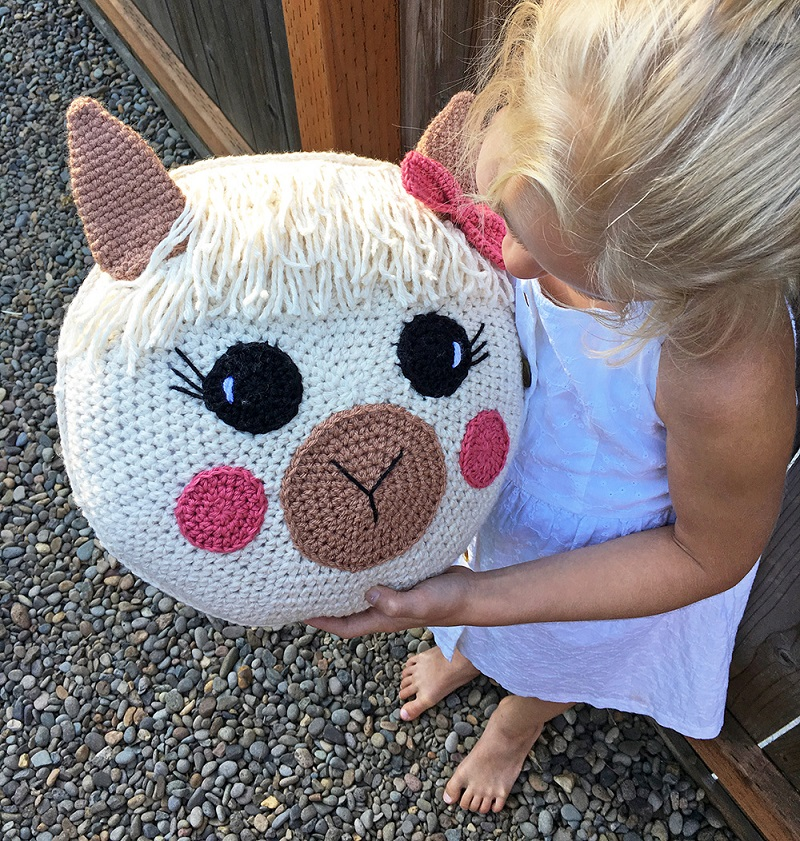 A photo of a barefoot blonde girl holding the crocheted amigurumi llama pillow
