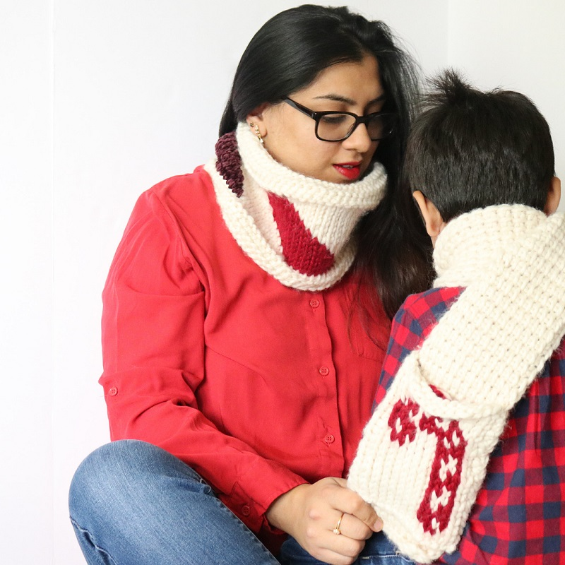 Photo of Noorain Nizami and a little boy wearing red shirts and the crocheted Tuni Candy Cane Scarf FREE pattern and cowl