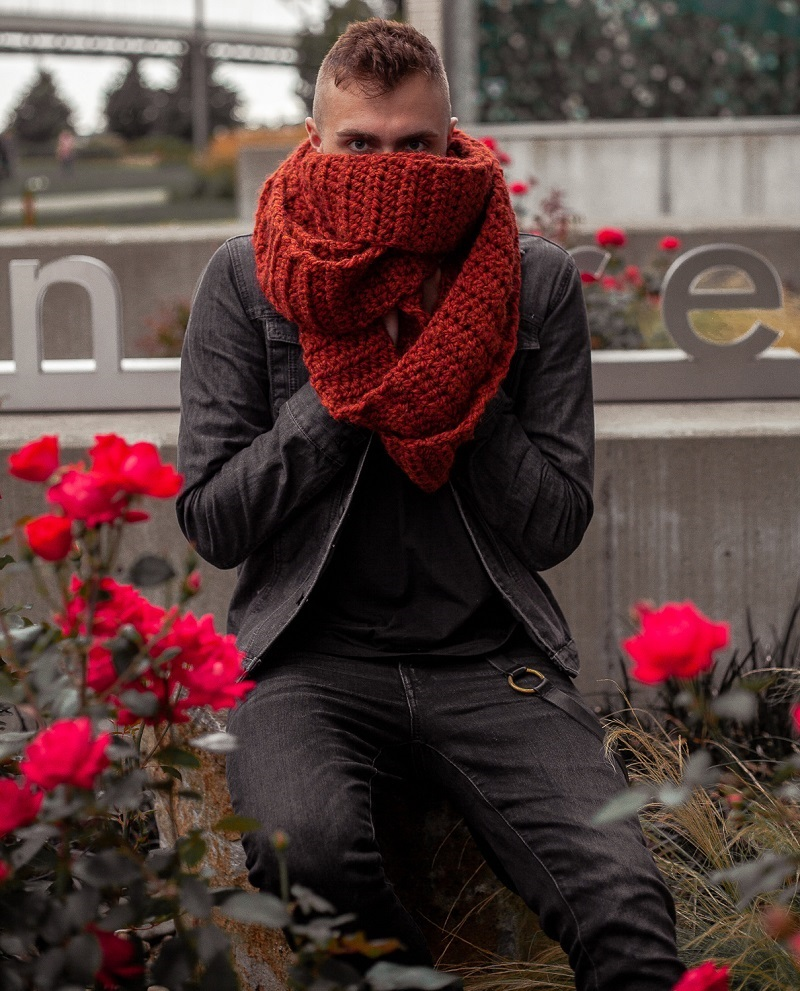 A man wearing a crocheted unisex infinity scarf in a deep rust color. The scarf is covering the lower half of his face.
