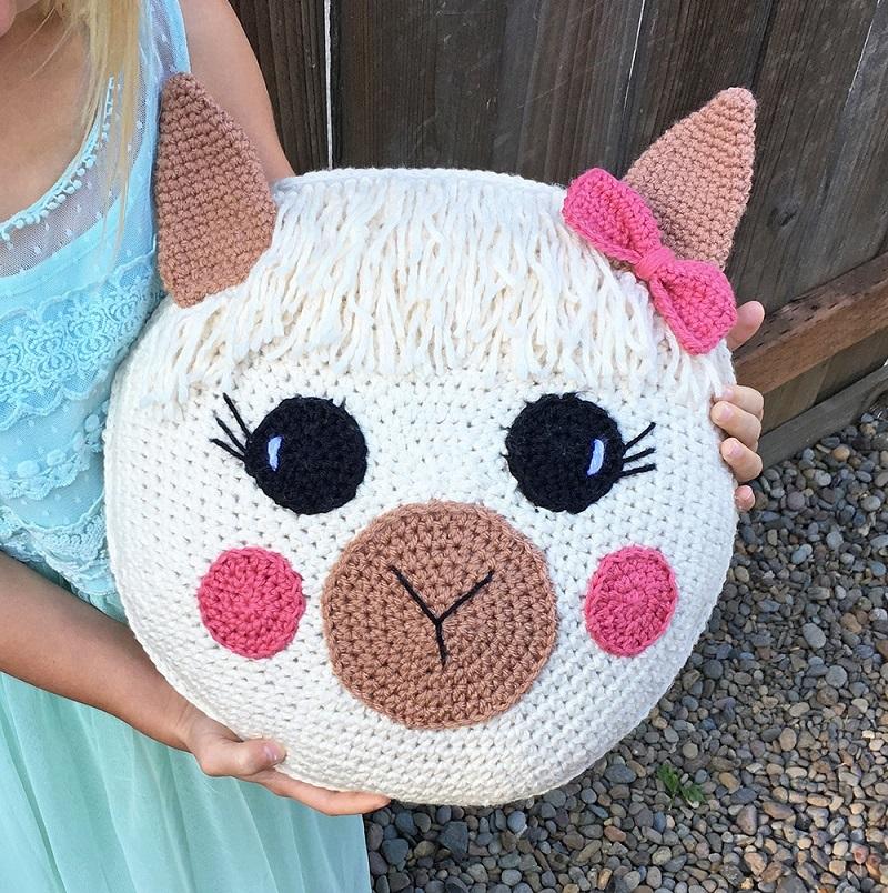 A girl holding the cute crocheted llama throw pillow