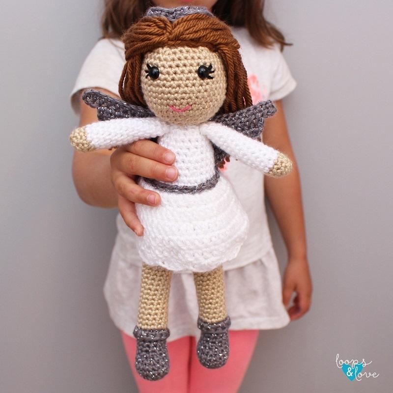 A little girl holding the crocheted amigurumi angel