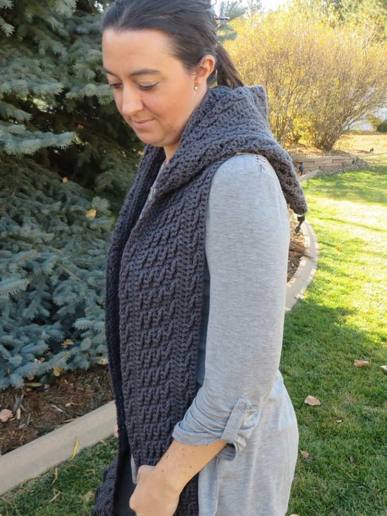 A woman wearing the crocheted textured hooded scarf while she is in the outdoors