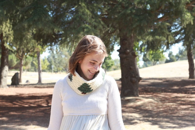 Photo of Claire enjoying the woods and her crocheted Pinewood Tapestry Cowl with a white long-sleeved shirt surrounded by trees while she is looking down