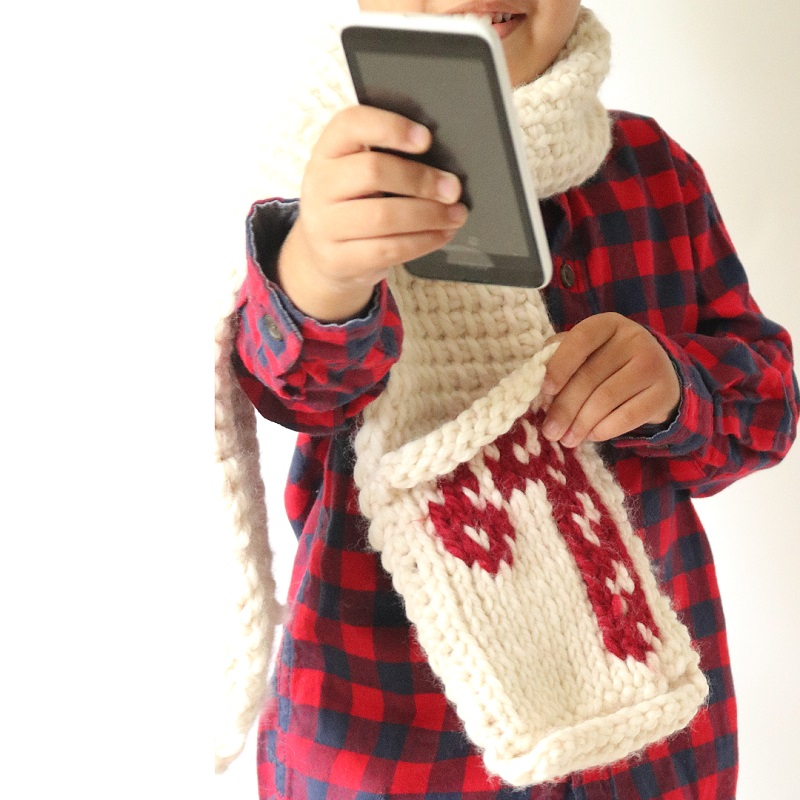 Photo of a little boy holding a phone and wearing a plaid red and black shirt and the Tuni Candy Cane Scarf neck warmer