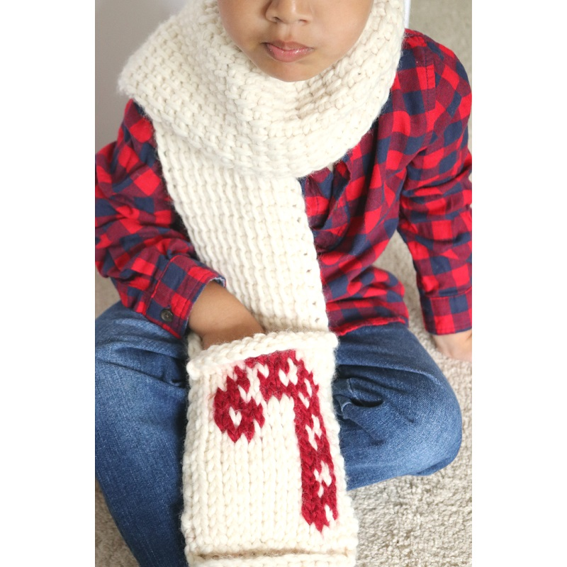 Photo of a little boy sitting on a soft carpet wearing the Tuni scarf and red and black plaid shirt with pands