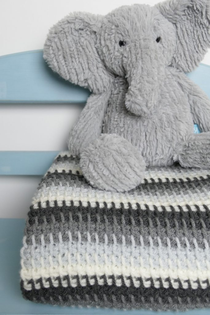 Photo of an elephant stuffed toy on top of the folded Tunisian baby blanket