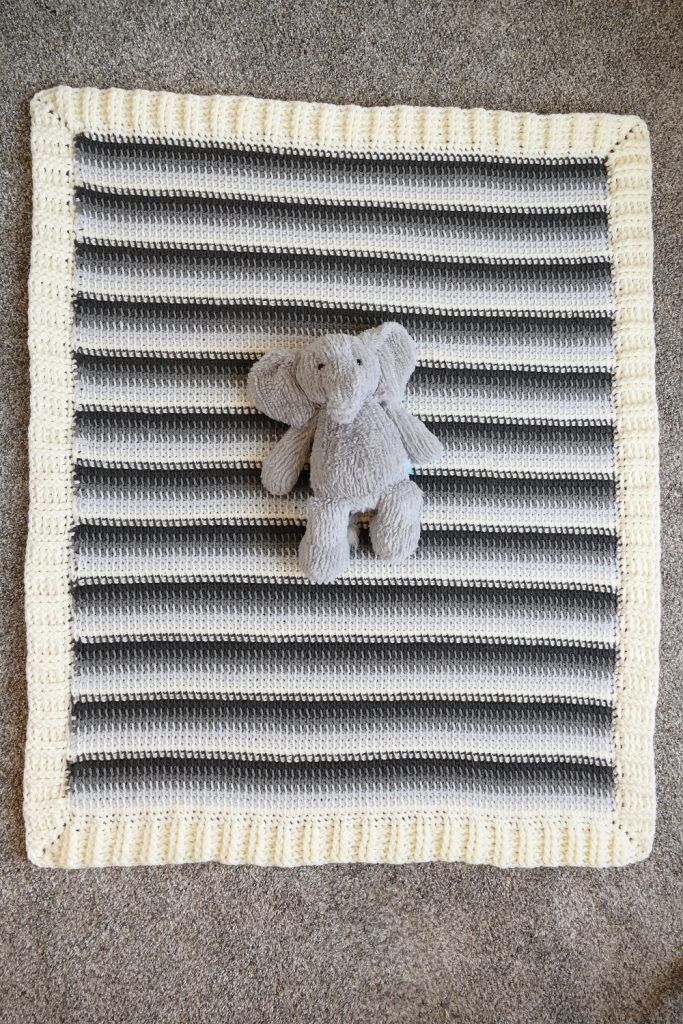 An elephant stuffed toy lying on top of the Tunisian Baby Blanket spread on a carpet