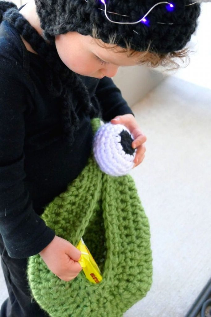 Photo of a kid using the crocheted green Alien Trick or Treat Bag