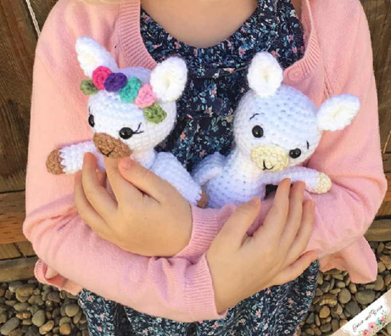 Photo of a girl holding miniature crocheted baby llama stuffed toys