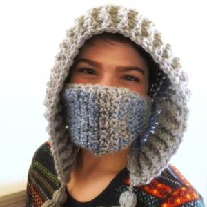 Photo of a woman wearing the crocheted winter hood and mask looking at the camera