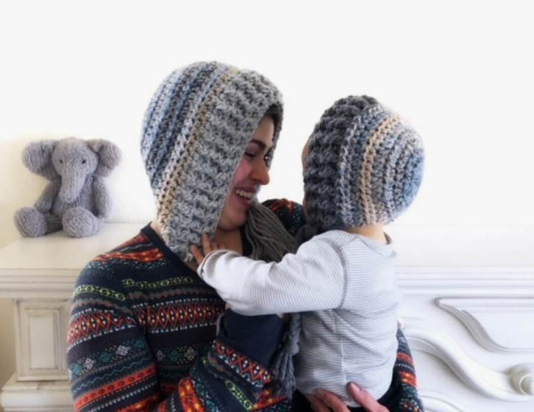 Photo of a woman and a child wearing the crocheted snow hood style hat and long sleeved shirt