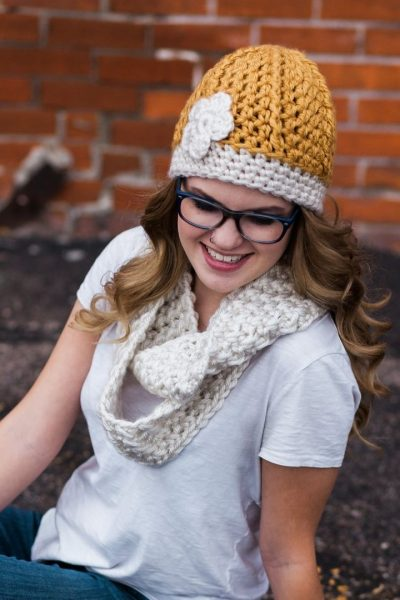 Image of a blond young woman sitting in a parking lot with a gold crochet hat. This is a Pinterest image. Click it to save to a Pinterest board.